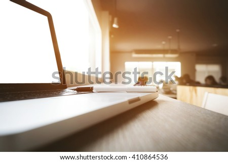 Close up of pen and laptop at office sunny day vintage tone. - stock photo