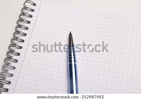 close up of pen on blank note book with checked pages - stock photo