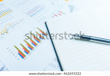 close up of pen on notepad with business documents in background. Business concept. Photo with selective focus and blue light filter.