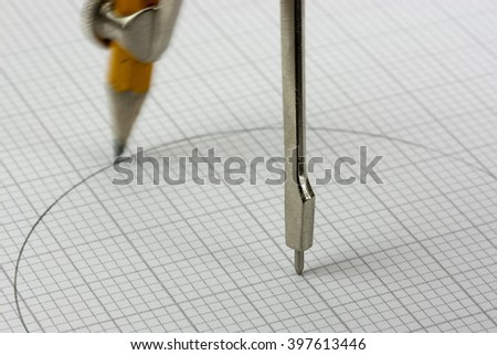 Close up of pencil drawing a circle on graph paper - stock photo