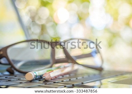 Close up of pencils and eyeglasses on laptop keyboard, soft focus  - stock photo