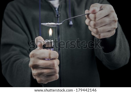 Close up of person cooking heroin using lighter - stock photo