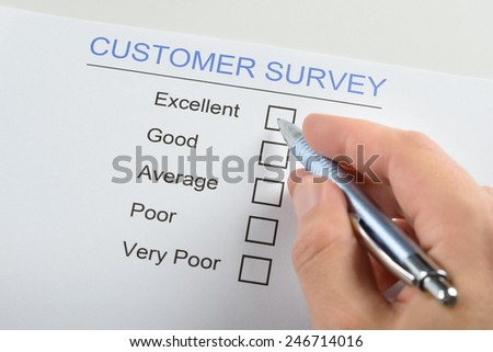 Close-up Of Person Hand Filling Customer Survey Form With Pen - stock photo