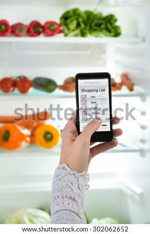 Close-up Of Person Hand With Mobile Phone Showing Shopping List On Display - stock photo