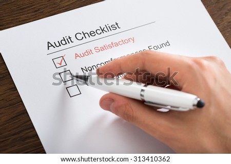 Close-up Of Person Hands Filling Audit Checklist Form With Pen At Desk - stock photo