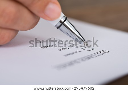 Close-up Of Person Hands Holding Pen Over Customer Survey Form - stock photo