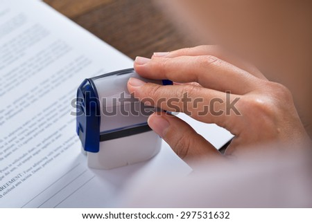 Close-up Of Person Hands Pressing Stamper On Document - stock photo