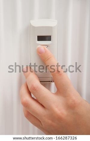 Close-up Of Person's Hand Adjusting Temperature With Digital Thermostat