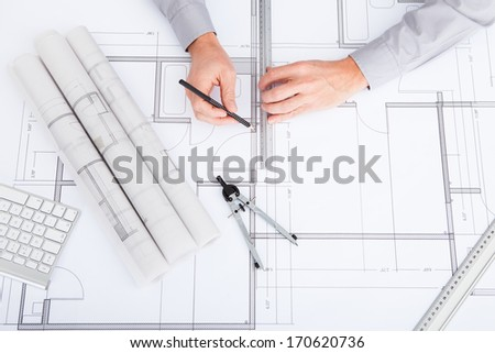 Close-up Of Person's Hand Drawing Plan On Blue Print - stock photo