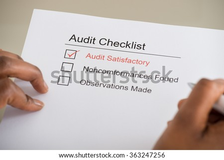 Close-up Of Person's Hand Filling Audit Checklist Form - stock photo