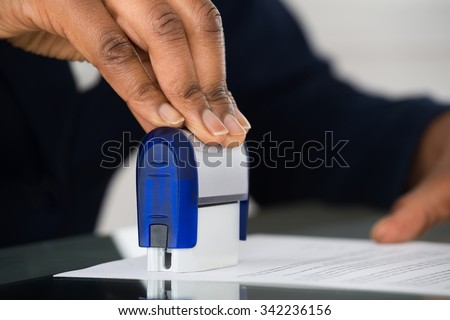 Close-up Of Person's Hand Stamping Document At Office Desk - stock photo