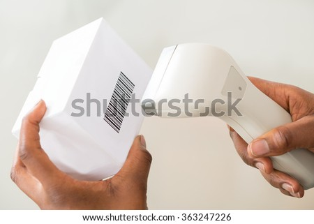 Close-up Of Person's Hand Using Barcode Scanner To Scan A Barcode On Product - stock photo