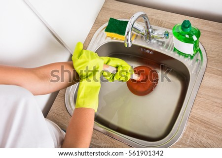 Close Up Of Person Using Plunger In The Kitchen Sink