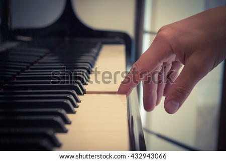 Close up of pianist forefinger touching piano key.      - stock photo