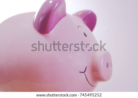 Close up of piggy bank. Ceramic money box in the shape of a pig. Smiling, pink.