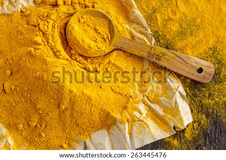 Close up of pile of organic turmeric (curcuma) powder sitting on brown paper with measuring spoon on wooden table - stock photo