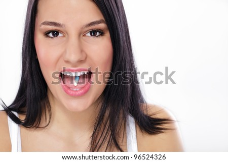 Close-up of pill in woman's mouth - stock photo