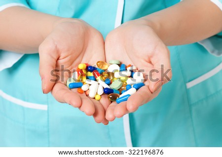 Close up of pills in woman hands - stock photo