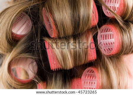 close-up of pink curlers in blond hair - stock photo