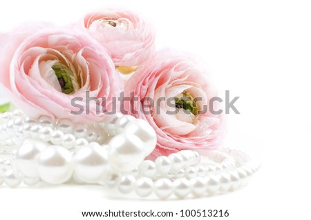 Close up of pink flowers and pearl beads on a white background - stock photo