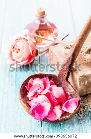 Close Up of Pink Rose Petals in Rustic Wooden Ladle in Spa Themed Still Life with Blue Painted Wooden Background with Handmade Soap, Delicate Pink Rose and Bottle of Essential Aromatic Oil - stock photo