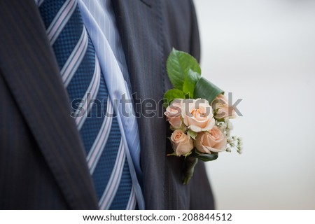 Close-Up of Pink Roses Boutonniere on Formal Black Tuxedo. - stock photo