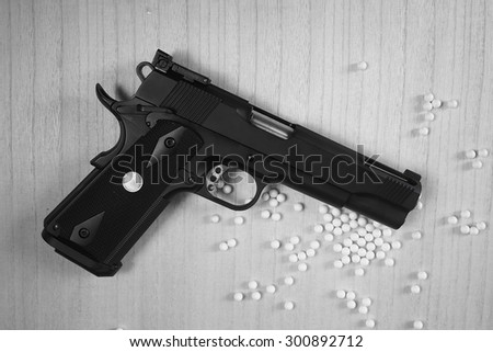 Close up of pistol. 11 mm or 0.45 and BB gun bullet. Black and White. - stock photo