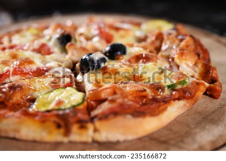 close up of pizza on wooden board. - stock photo