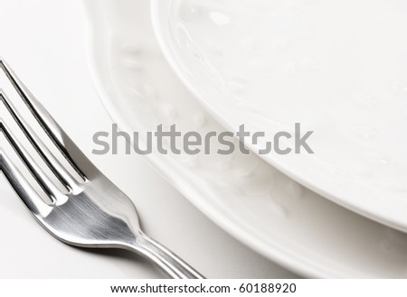Close up of place setting with white plates and fork. - stock photo
