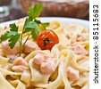 close-up of plate of pasta and smoked salmon with tomato - stock photo