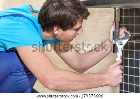 Close up of plumber in blue overalls in work
