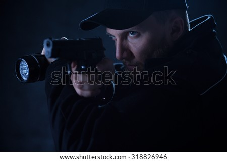 Close-up of policeman holding gun and flashlight - stock photo