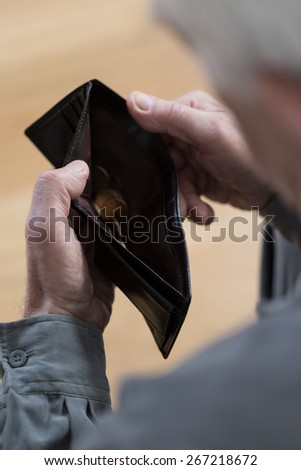 Close-up of poor senior man holding empty wallet