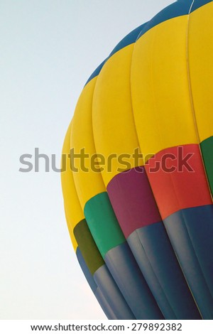 Close up of portion of rainbow colored hot air balloon against sky. - stock photo