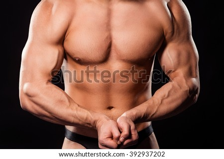 Close-up of posing bodybuilder's torso. Huge torso of muscular athlete. Nice body composition. The future champion. - stock photo