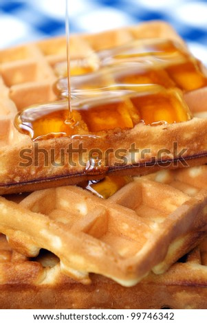 Close-up of pouring honey on waffles - stock photo
