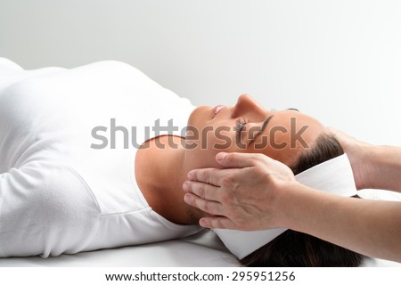 Close up of practitioner doing reiki with hands on young woman. Therapist doing healing treatment with hands next to head. - stock photo