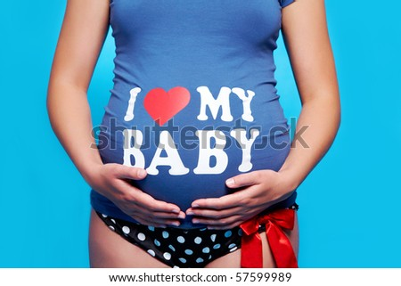 Close-up of pregnant woman touching her stomach over blue background - stock photo
