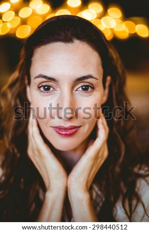 Close up of pretty brunette with hands under her chin looking at camera at the bakery store - stock photo