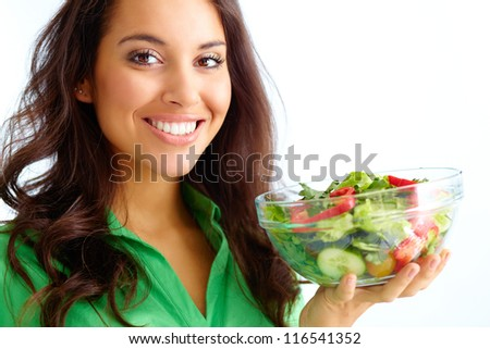 Close-up of pretty girl holding fresh vegetable salad in glass bowl - stock photo