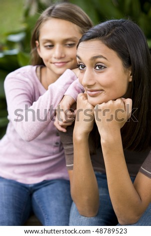 Close-up of pretty teenage girl and younger sister smiling - stock photo