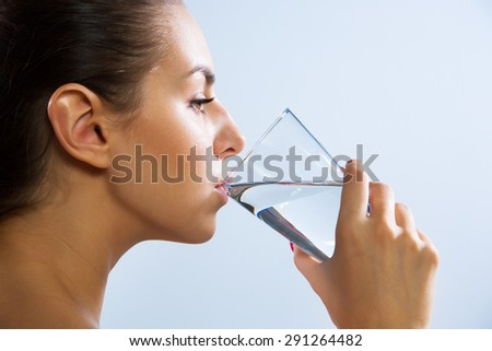 Close-up of pretty young woman drinking water from glass - stock photo