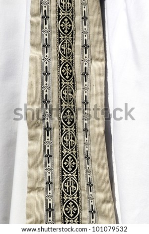 Close up of priests garment clothing decorated with small crosses on white wearing. - stock photo
