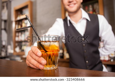 Close up of professional bartender serving self-made cocktail. He is holding glass and standing at counter. The man is smiling. Focus on drink
