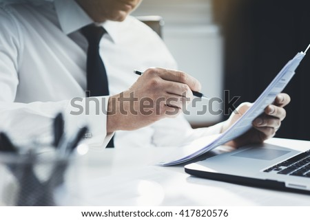 Close-up of professional businessman working at his office with documents, young lawyer using laptop computer and signing contract at comfortable interior, flare light - stock photo