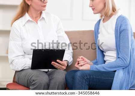 Close up of professional psychologist consulting young woman. They are sitting on sofa and talking. The girl is explaining her feelings with sadness - stock photo