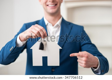 Close up of professional realtor holding a key and placard in shape of house. He is pointing finger at it. The man is standing and smiling - stock photo