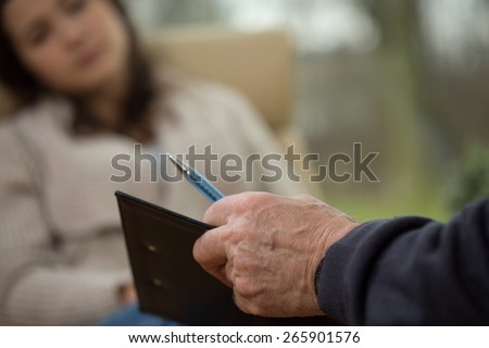 Close-up of psychologist writing down patient's history - stock photo