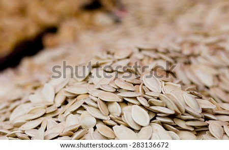 Close up of pumpkin seeds in peels on pile - stock photo