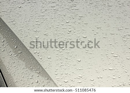 Close up of rain water droplets patterns and textures on wet metal panels of silver motor vehicle